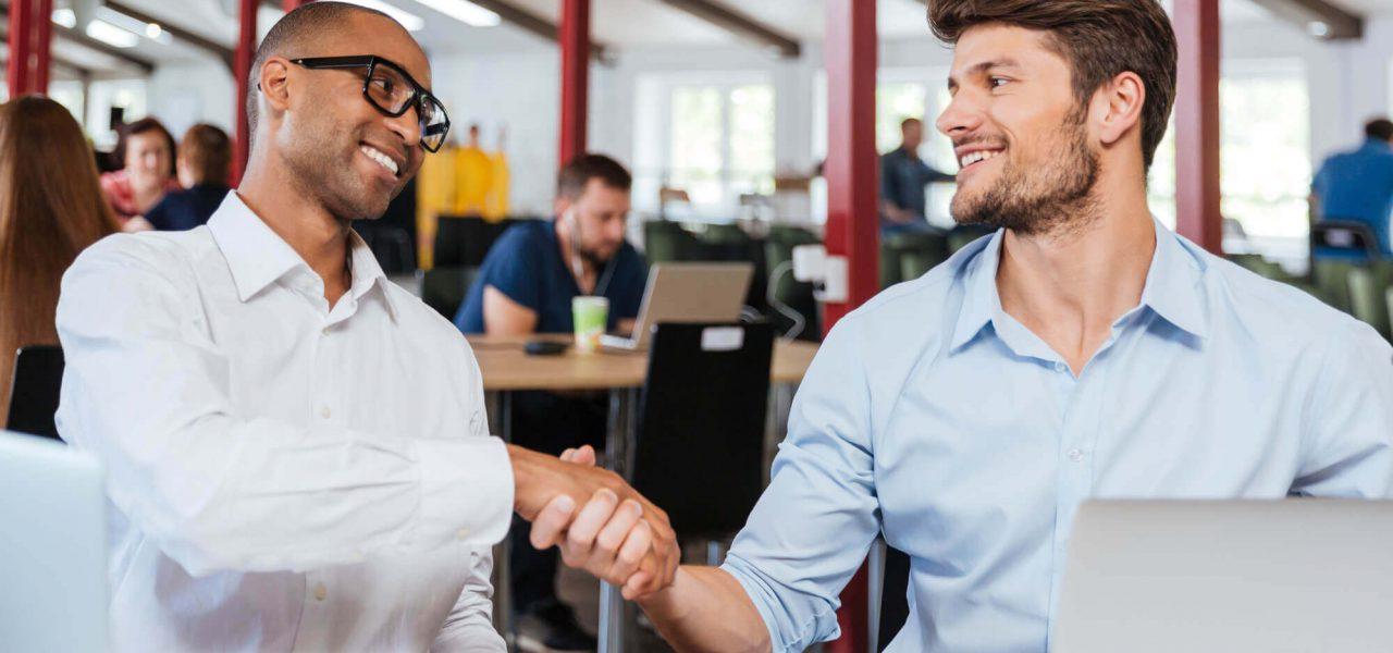 Fotografia de dois homens dando um aperto de mãos