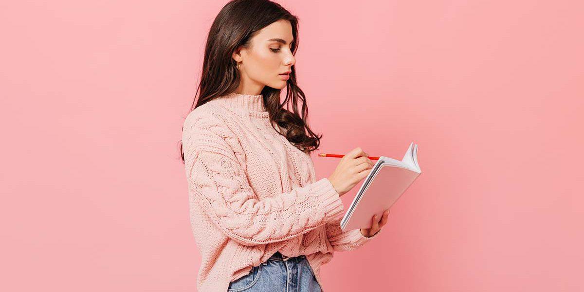 Imagem de uma mulher fazendo anotações em um caderno