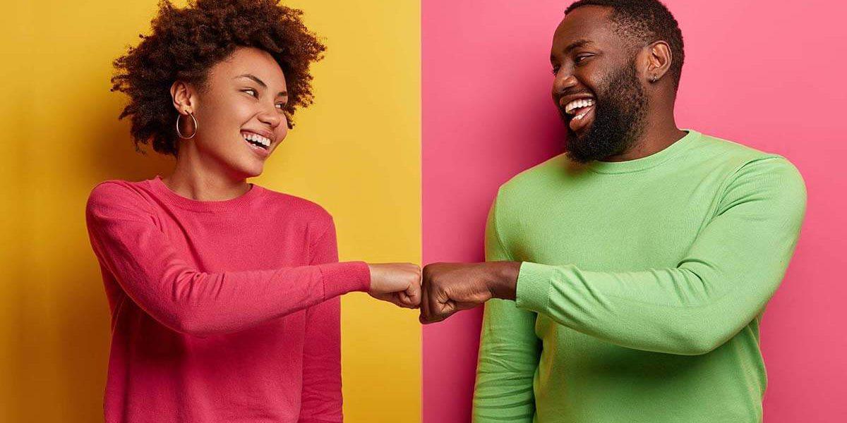 Fotografia de uma mulher e um homem sorrindo e dando um soquinho com as mãos, como forma de cumprimento