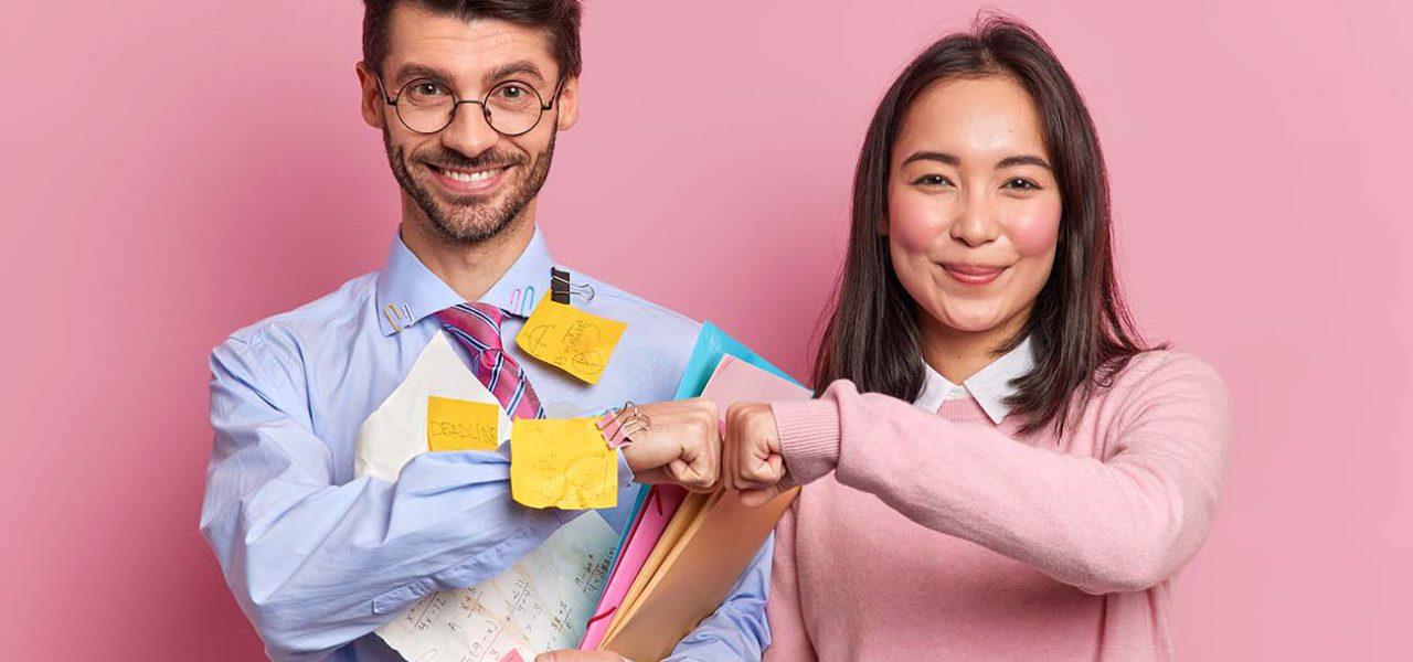 Fotografia de um homem e uma mulher sorrindo para a câmera, o homem está segurando alguns papéis e tem post-its espalhados pela roupa. A mulher veste um cardigan rosa. Eles estão se cumprimentado com as mãos.