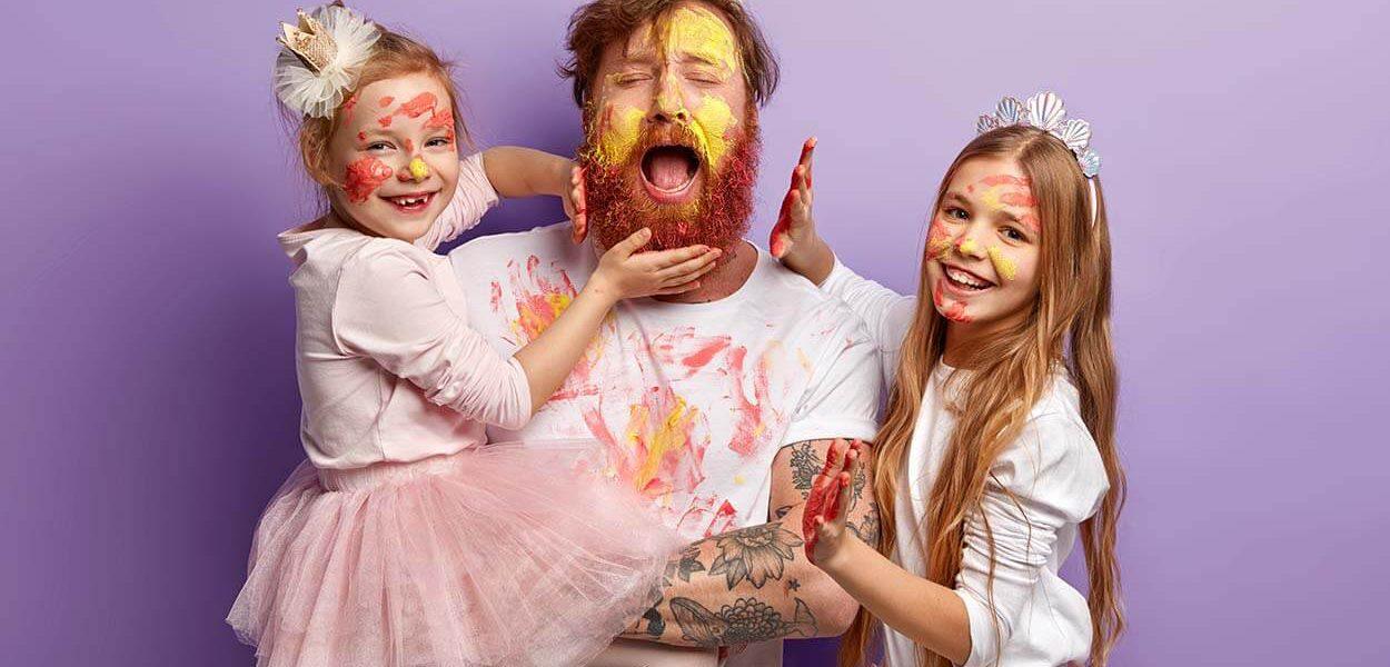 Fotografia de um pai com suas filhas, todos olham para a câmera com reação de alegria, enquanto brincam com tintas e fantasias.