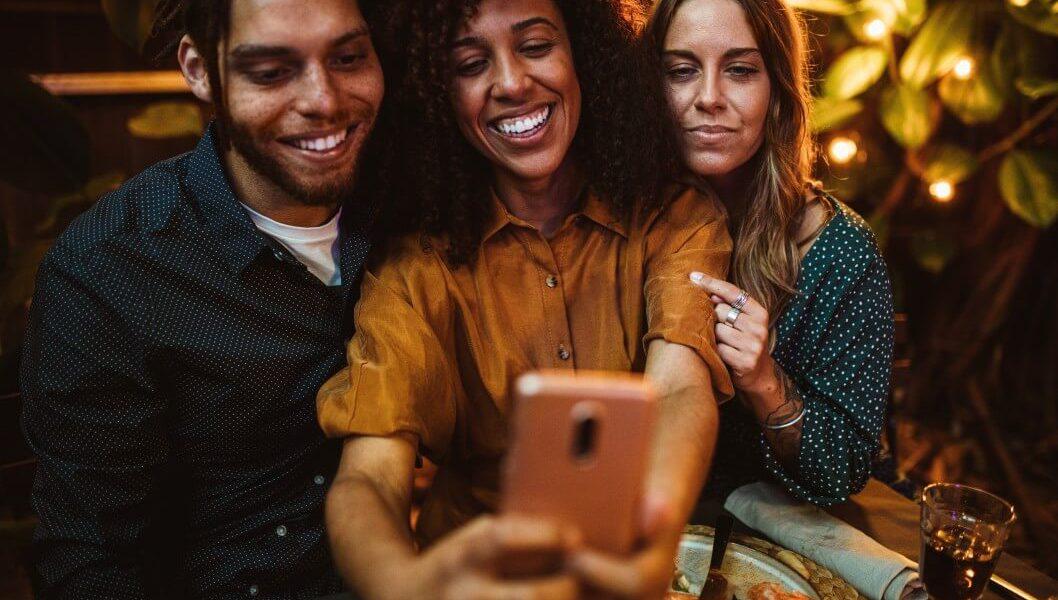 Duas mulheres e um homem tirando uma selfie com um telefone celular