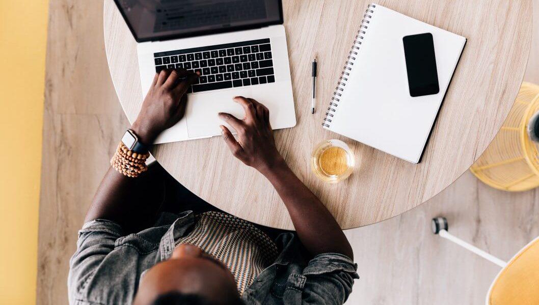Foto com a visão aérea de uma mesa com computador, caderno, celular e um jovem empresário trabalhando