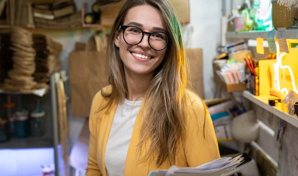 Mulher loira de ôculos, vestindo uma camiseta branca e casaco amarelo, sorrindo para a câmera e segurando algumas folhas de papel. Ao fundo, as prateleiras de estoque de uma loja, com algumas sacolas de papel à mostra e outros materiais diversos.
