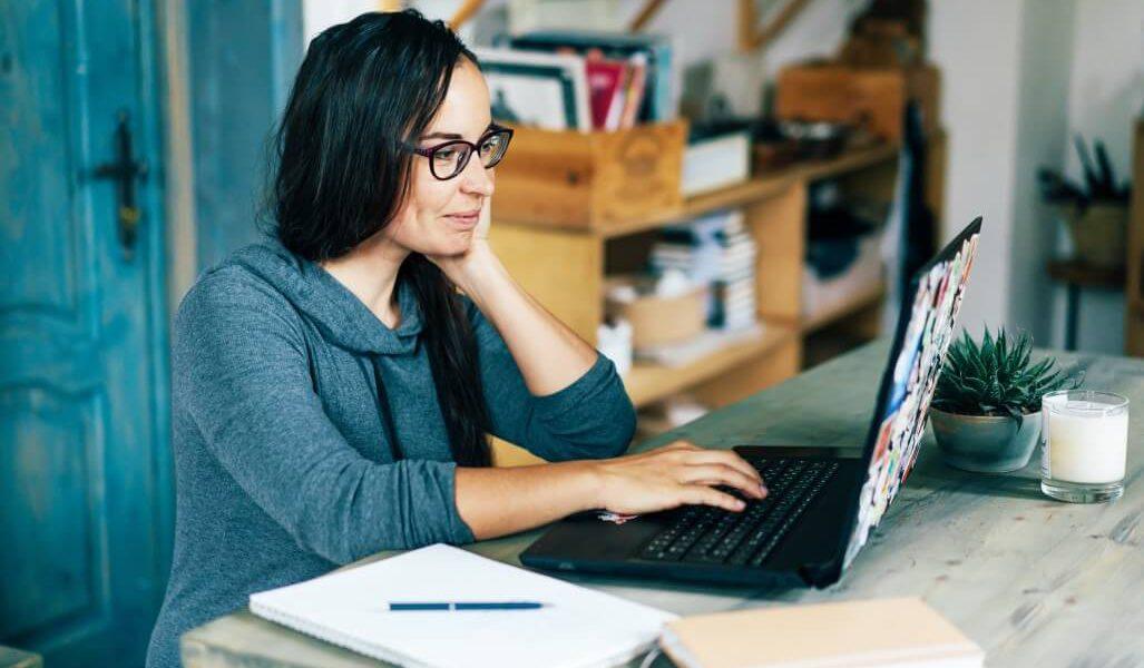 Mulher com cabelos pretos e ôculos de grau, usando uma blusa de manga comprida cinza utilizando um notebook.