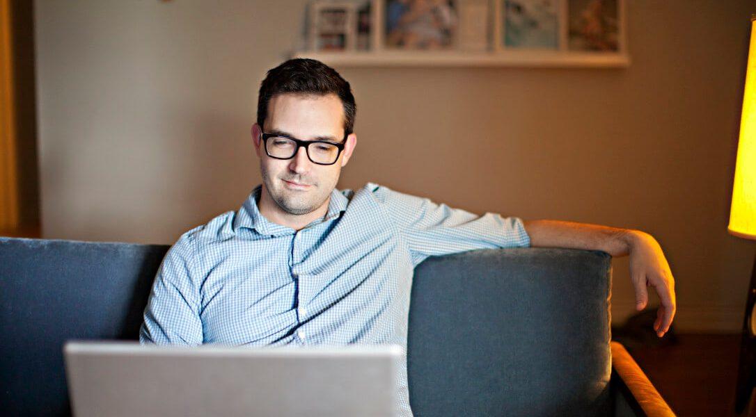 Homem branco com óculos de grau e camisa azul, sentado em um sofá e usando notebook.