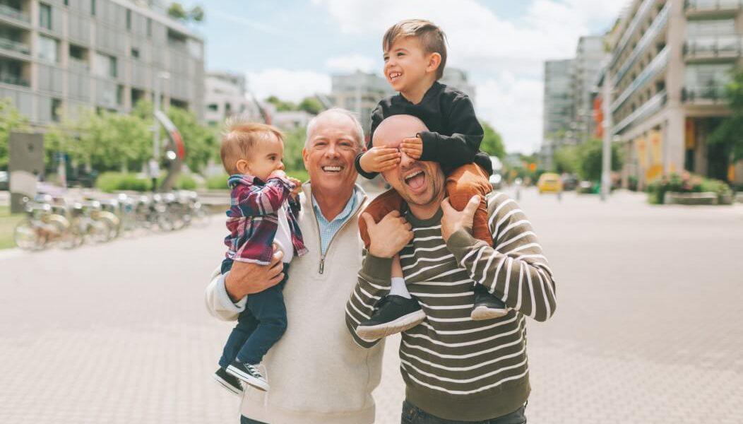 O retrato de um senhor com seu filho e dois netos  sorrindo em uma praça de cidade grande