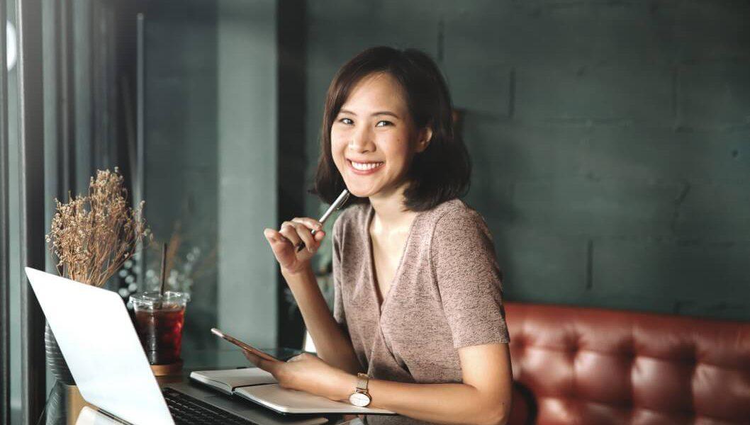 Mulher sorridente utilizando um laptop