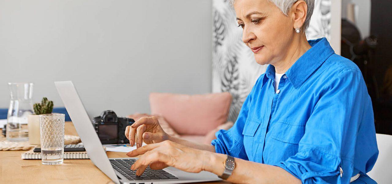 Fotografia de uma senhora utilizando um notebook