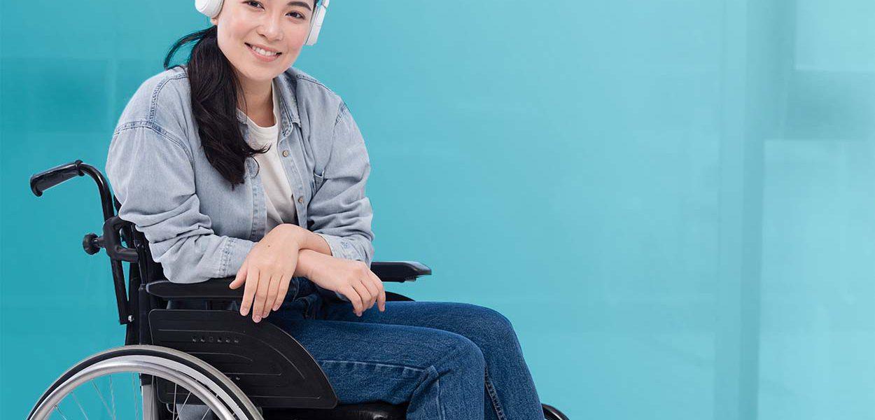 Imagem de uma jovem mulher cadeirante, usando fones de ouvido e sorrindo para o leitor