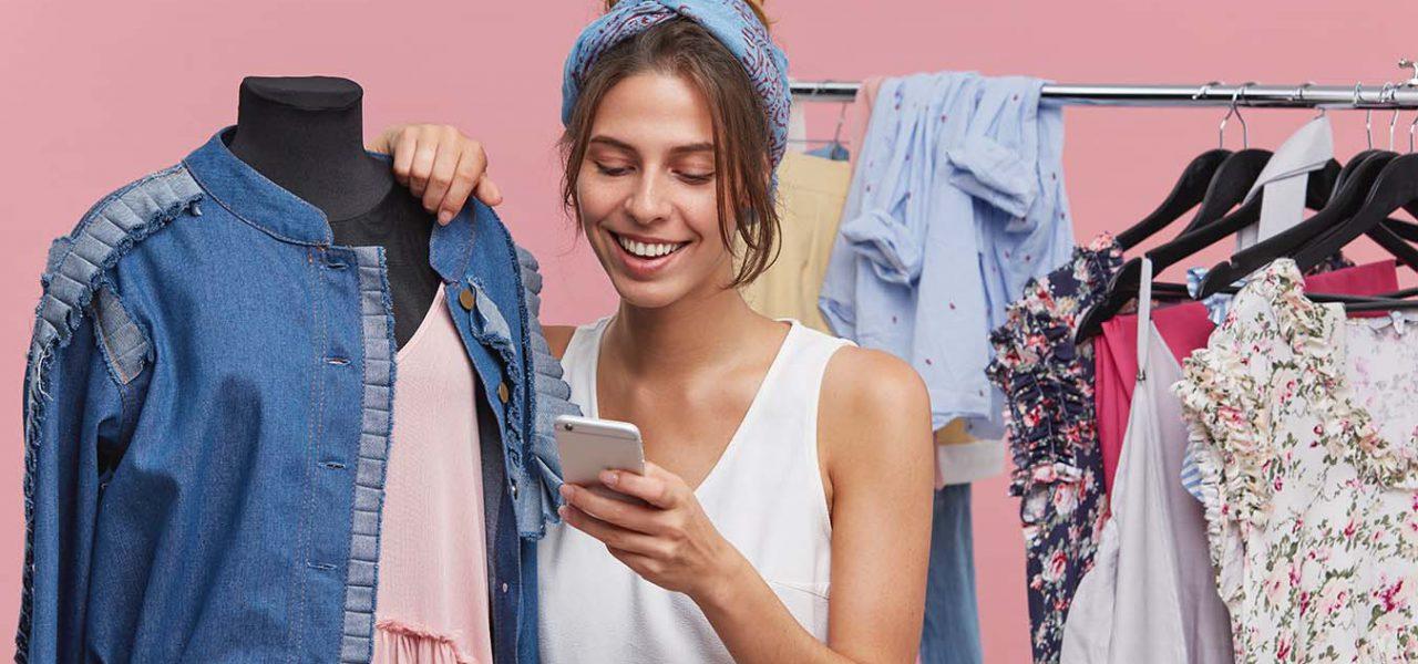 Fotografia de uma mulher usando um celular e sorrindo, ela está se apoiando em um manequim de loja de roupas e no fundo temos uma arara de loja com alguns cabides e peças de roupa pendurados