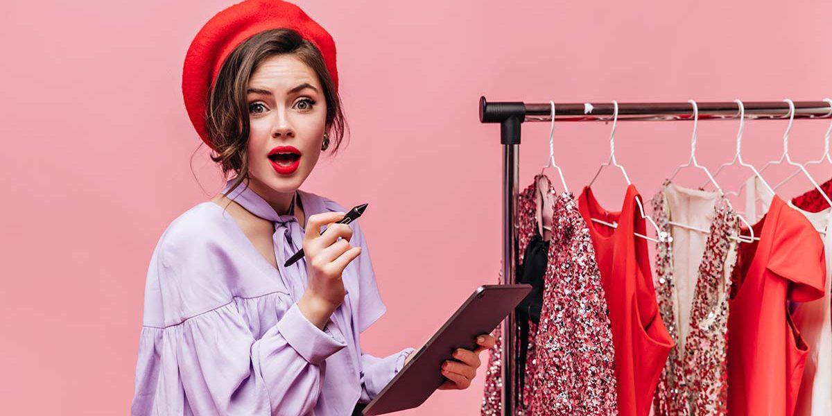 Fotografia de uma mulher olhando para a câmera com cara de surpresa, segurando uma caneta digital e um tablet. Ao seu lado, uma arara com roupas penduradas.