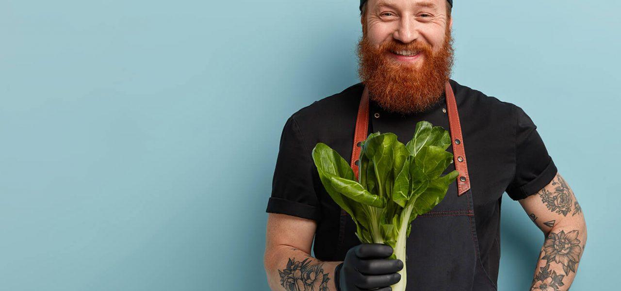 Fotografia de um homem sorrindo para câmera, ele usa um boné, avental e segura um ramo de verduras na mão.