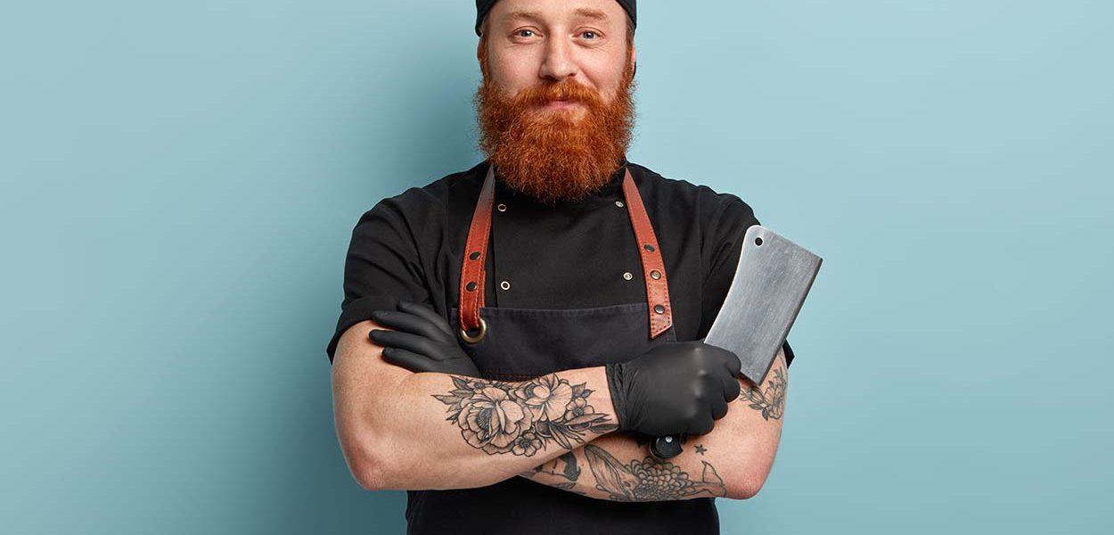 Fotografia de um homem sorrindo para câmera, ele usa um boné, avental e segura uma faca para cortar carnes