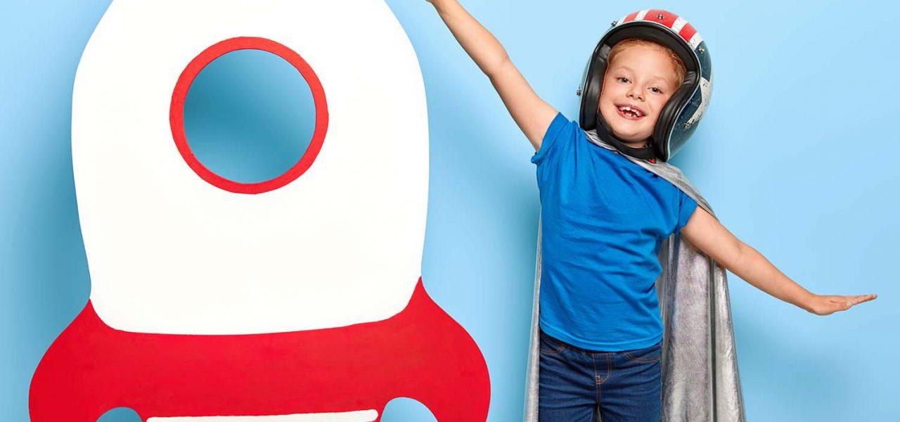 Fotografia de uma criança sorrindo e brincando ao lado de um foguete feito de papelão