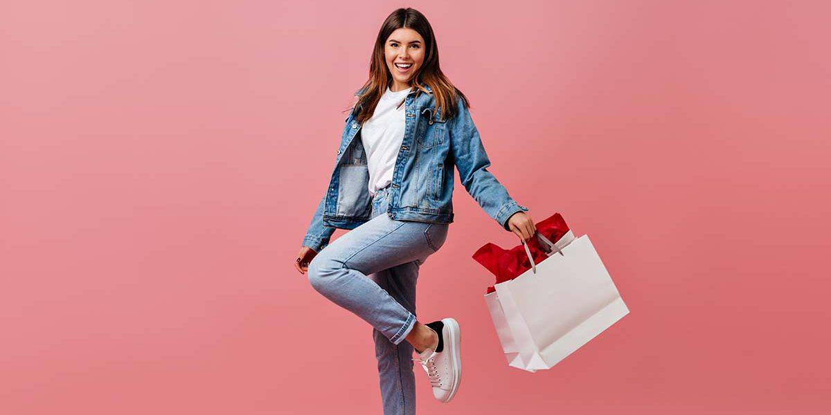 Imagem de uma mulher sorrindo com sacolas de compras