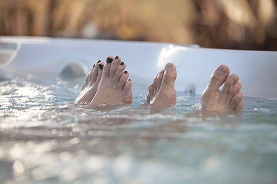 a close-up image of a couples toes peaking out of the water in a portable hot tub