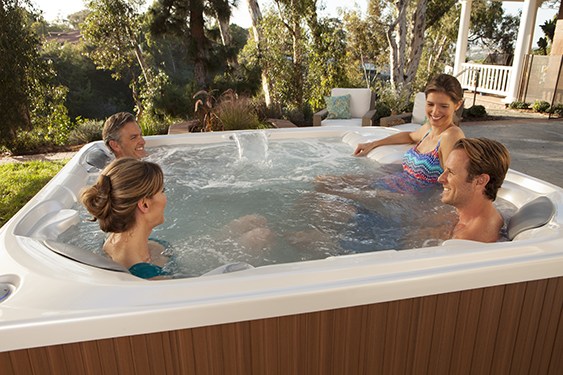 a group of four friends enjoy a hot tub soak in a limelight flair spa on a sunny day