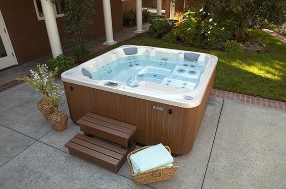 a limelight flair portable hot tub sits on a backyard patio