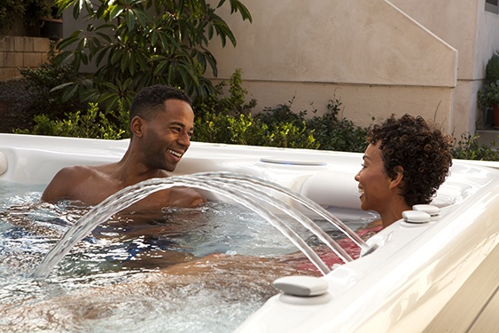 a couple enjoying a relaxing soak in a highlife aria NXT spa in a backyard on a sunny day