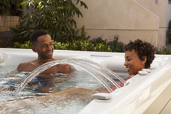 a couple relaxes in a highlife nxt jacuzzi with a bellafontana fountain