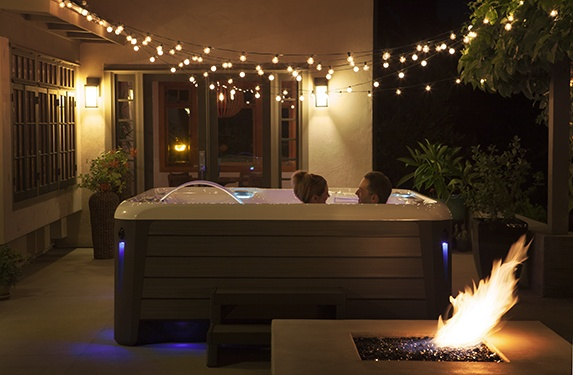 a couple enjoying a lovely evening in a highlife aria NXT spa with a lit firepit in the front and twinkling tiny patio lights overhead