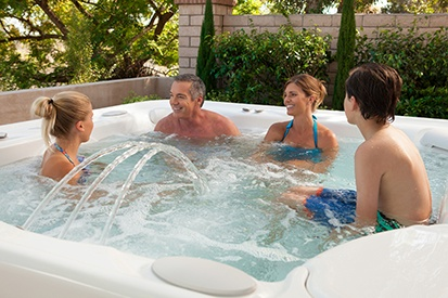 family enjoys relaxation techniques in a hot tub similar to a sauna