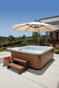 an image of a highlife sovereign spa on a sunny patio demonstrating the use of a spa side umbrella