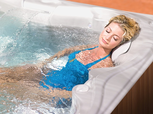 an image of a woman relaxing in her hot tub to relieve stress and prepare for good sleep