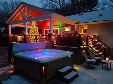 a hot tub at dusk in a snowy christmase scene with colored lighting