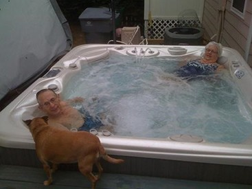 couple enjoys powerful hot tub hydro massage therapy while their dog watches from outside the spa