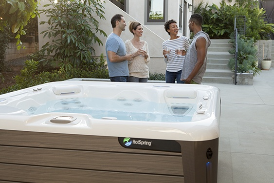 4 friends relax and chat on a beautiful backyard pation with their high quality aria nxt hot tub in the forefront