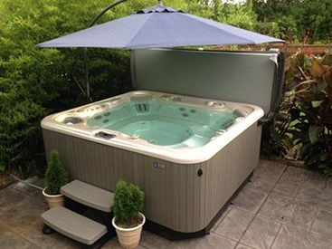 a grandee hot tub with a spa side umbrella on an owners patio