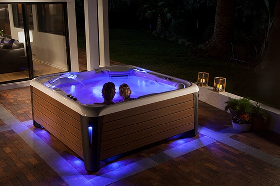 an image of a couple relaxing in a hot tub in a nighttime setting to prepare for a better night's sleep