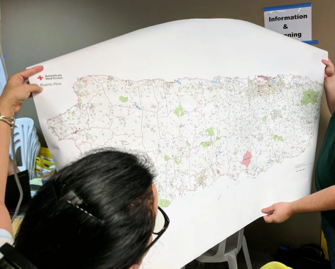 Red Cross volunteers in San Juan, PR hold up a map of Puerto Rico.