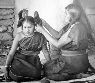 A Hopi woman dresses the hair of an unmarried girl, circa 1900.