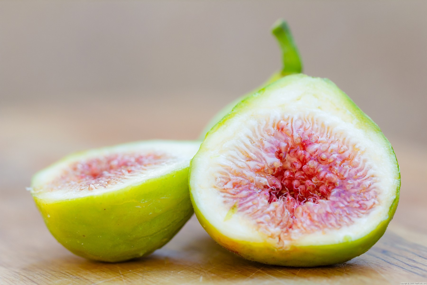A halved and whole fig isolated on a wooden board