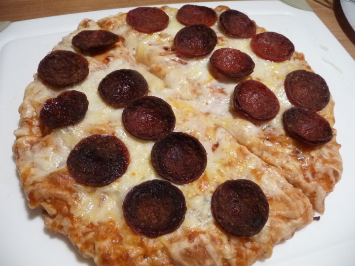 Sliced microwaved pepperoni on pizza