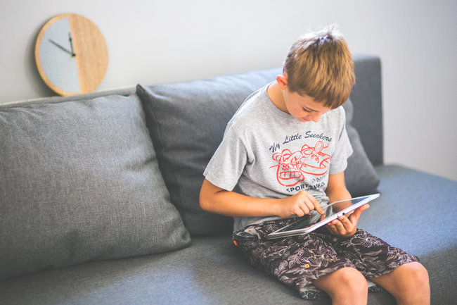 kaboompics.com_Young boy sitting on sofa with tablet pc-ipad-child-teen-stock