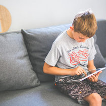 Kaboompics com young boy sitting on sofa with tablet pc ipad child teen stock
