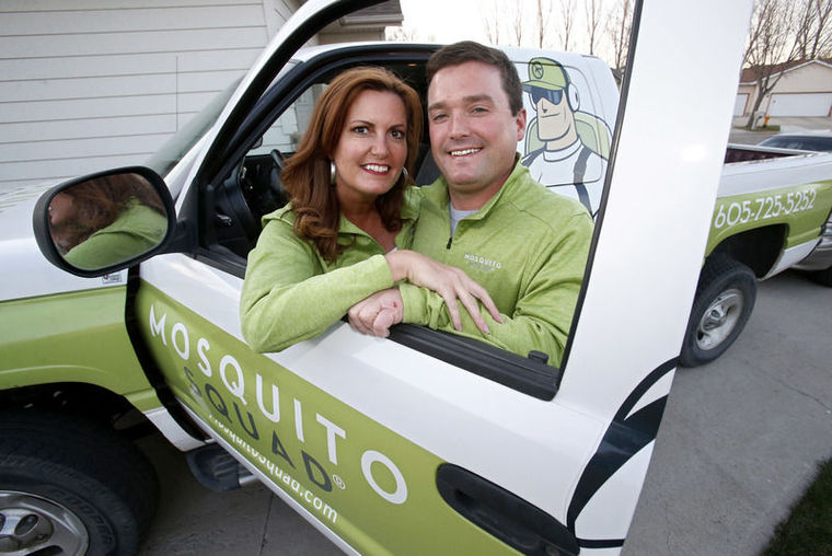 Greg Tople and his wife smile with their company vehicle.