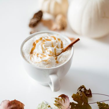 A mug of crockpot caramel apple cider topped with whipped cream, caramel and a cinnamon stick.