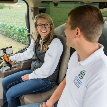 SDSU precision agriculture student learns how to operate technology and equipment in the cab of a combine with professor.