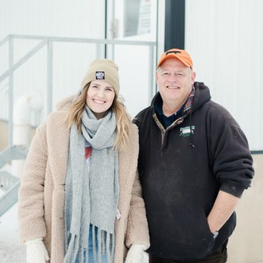 Oksana smiles with Steve Rommereim on his pig and soybean farm in Alcester, South Dakota.