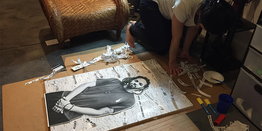 A person kneels on the floor indoors, working on decoupaging strips of paper with text on the background of a black-and-white portrait of a black man.