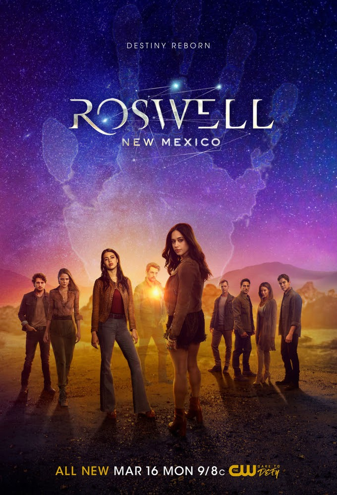 A show poster for Roswell, New Mexico. Underneath the show title in sleek silver letters, several people stand in the desert under a starry, richly colored sky with a ghostly handprint filling the sky. Low hills rise in the background.