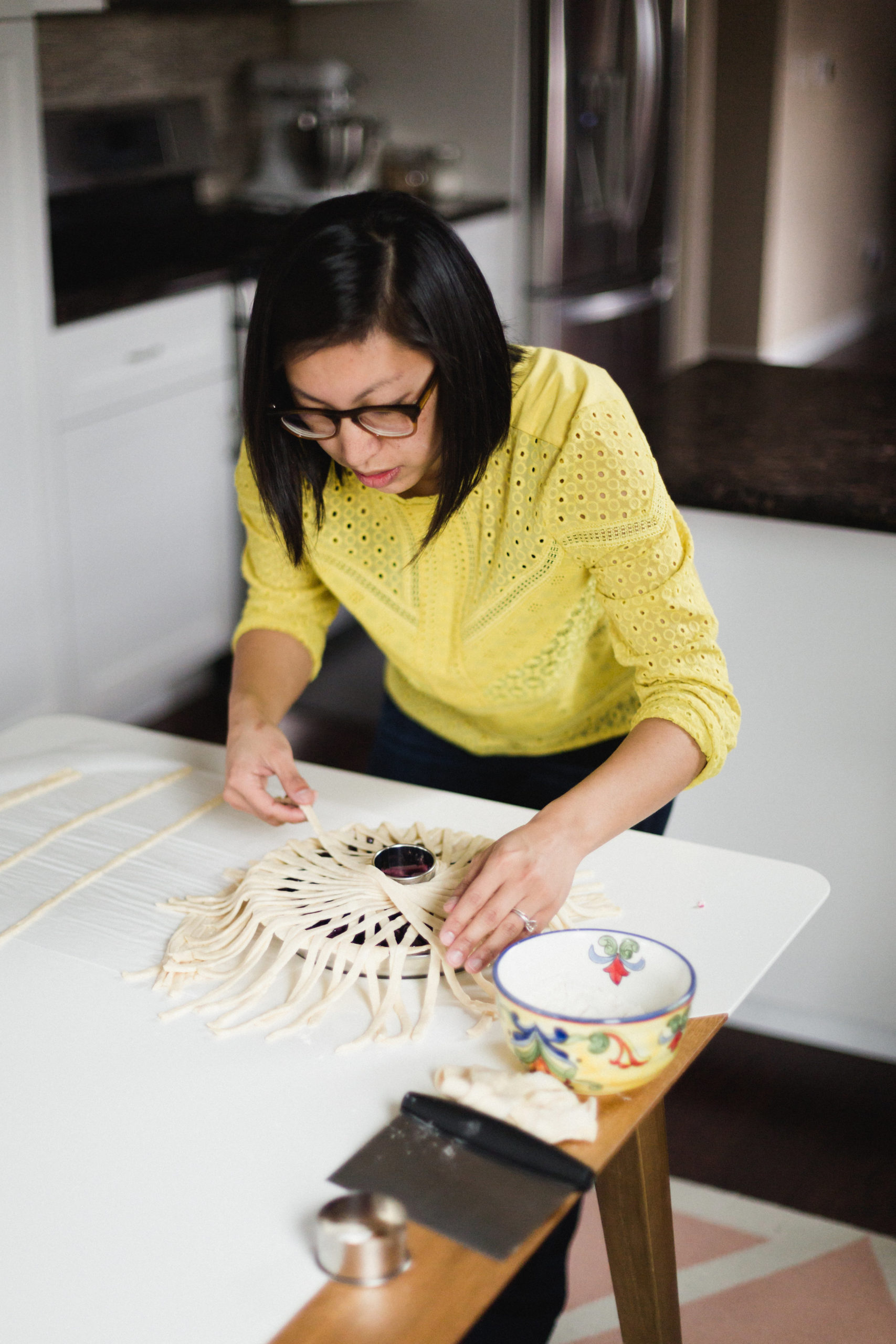 Lauren Ko leans intently over a pie, laying long strips of dough in an intricate pattern over the topping.
