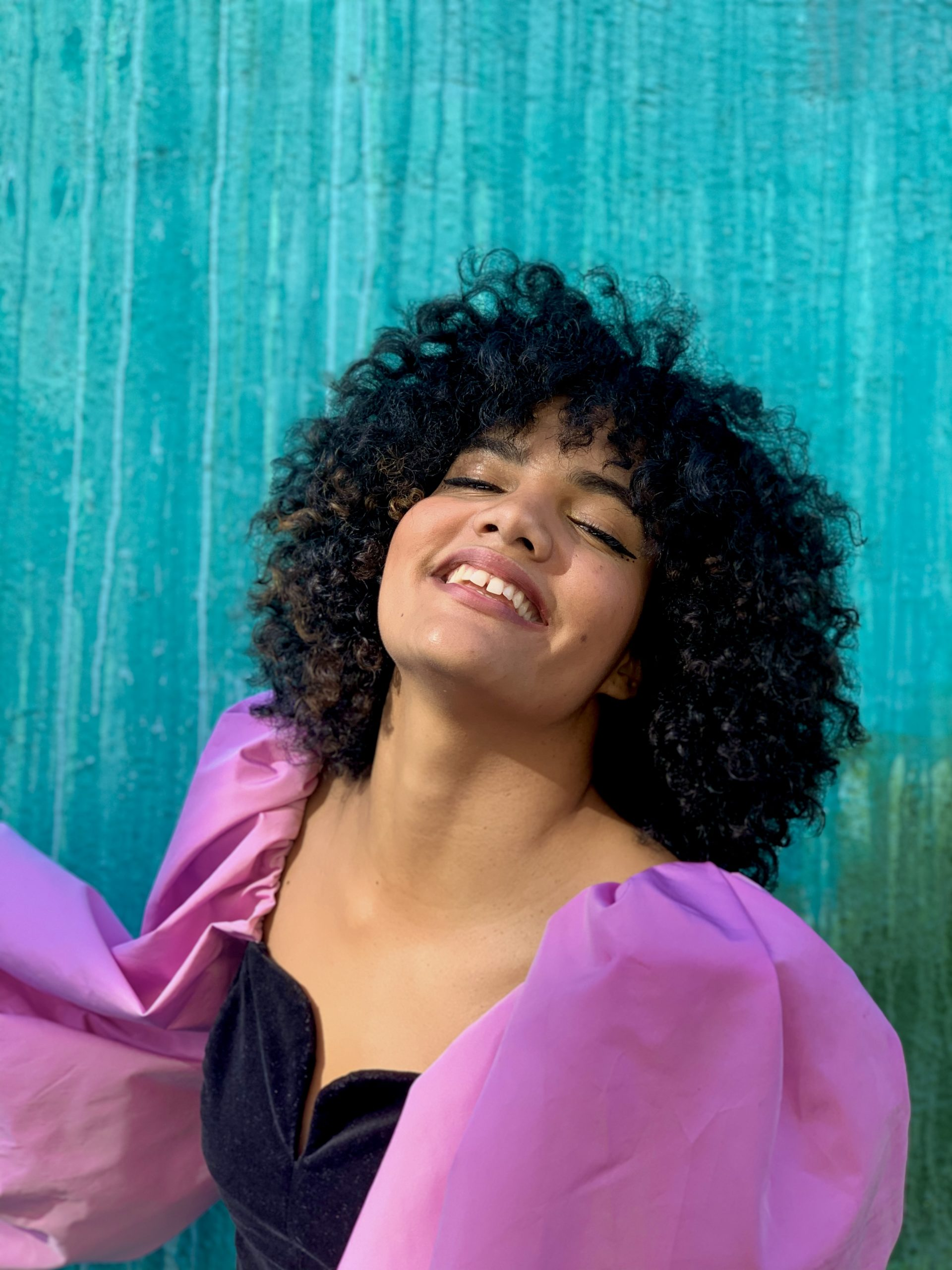 An Afro-Latina woman in a dark blue velvet top with voluminous fuschia sleeves throws her head back, smiling, in front of an aquamarine fabric backdrop. She has natural hair in a cloud around her head.
