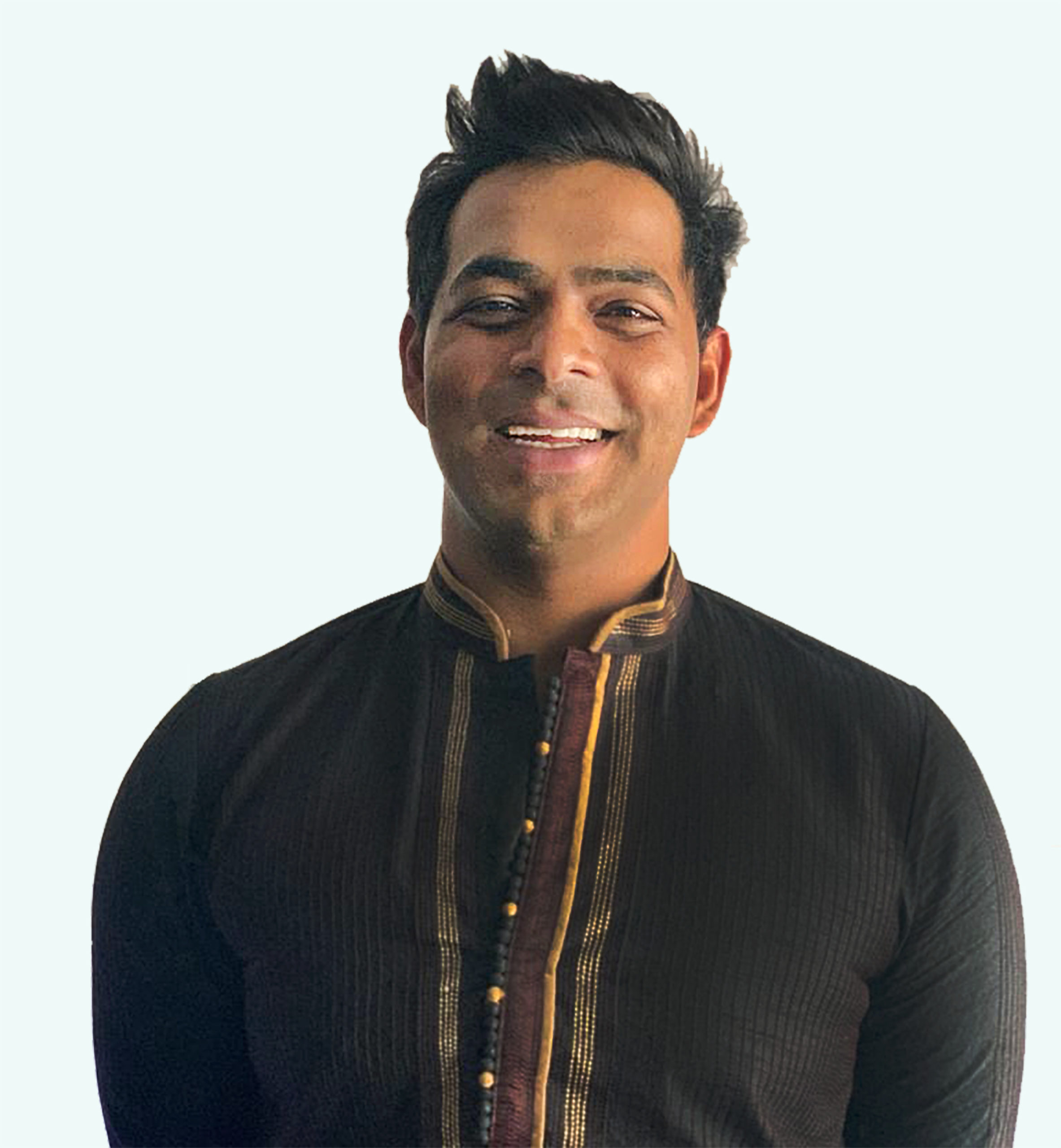 A smiling Indian man from the waist up, in a traditional black achkan sherwani with burgundy and gold trim.