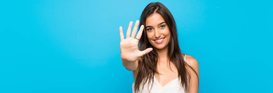 Mulher apontando o 5 com as mãos;